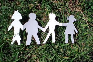 Paper cut out of family on grass